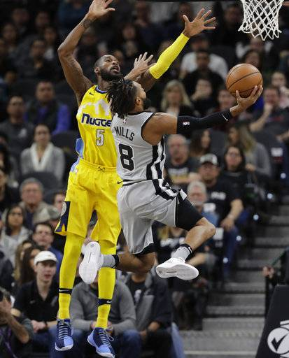 San Antonio Spurs guard Patty Mills (8) drives past Denver Nuggets guard Will Barton (5) during the first half of an NBA basketball game Saturday, Jan. 13, 2018, in San Antonio.