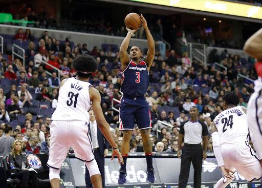 Washington Wizards guard Bradley Beal (3) shoots between Brooklyn Nets center Jarrett Allen (31) and forward Rondae Hollis-Jefferson (24) during the overtime portion of an NBA basketball game Saturday, Jan. 13, 2018, in Washington. The Wizards won 119-113 in overtime. (AP Photo/Alex Brandon)