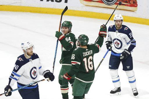 Minnesota Wild's Mikael Granlund (64) looks back at teammate Jason Zucker (16) after Granlund scored a goal against the Winnipeg Jets in the first period of an NHL hockey game Saturday, Jan. 13, 2018, in St. Paul, Minn.