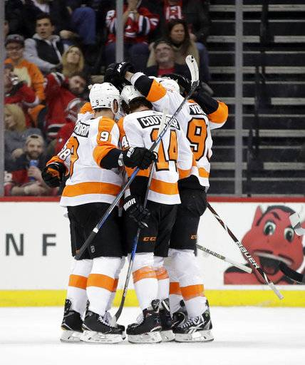 Philadelphia Flyers players celebrate a goal by Sean Couturier (14) against the New Jersey Devils during the second period of an NHL hockey game, Saturday, Jan. 13, 2018, in Newark, N.J.
