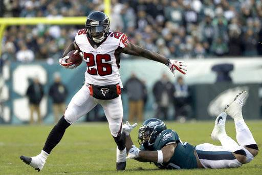 Atlanta Falcons' Tevin Coleman (26) slips past Philadelphia Eagles' Mychal Kendricks (95) during the first half of an NFL divisional playoff football game, Saturday, Jan. 13, 2018, in Philadelphia.