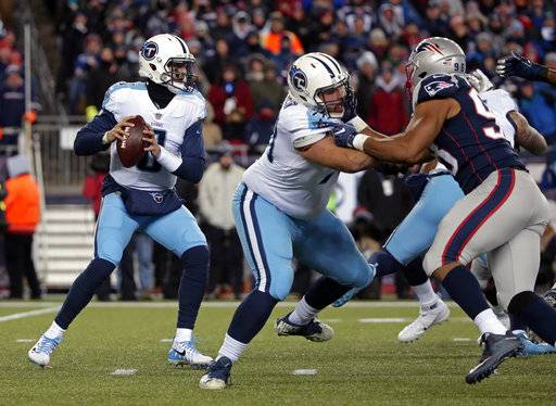 Tennessee Titans quarterback Marcus Mariota, left, looks for a receiver under pressure from New England Patriots defensive end Trey Flowers, right, during the first half of an NFL divisional playoff football game, Saturday, Jan. 13, 2018, in Foxborough, Mass.