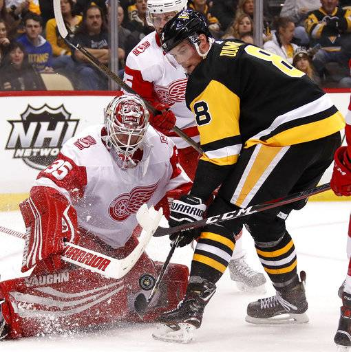 Pittsburgh Penguins' Brian Dumoulin (8) can't get his stick on a rebound in front of Detroit Red Wings goaltender Jimmy Howard (35) in the second period of an NHL hockey game in Pittsburgh, Saturday, Jan. 13, 2018.
