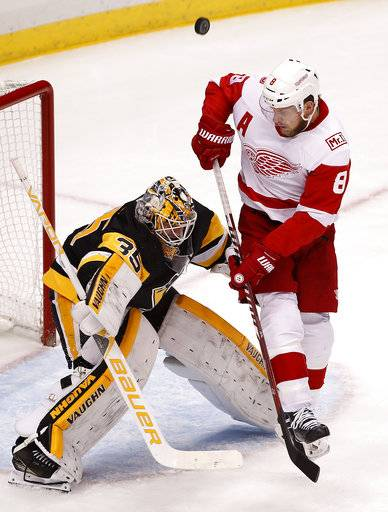 Pittsburgh Penguins goaltender Tristan Jarry (35) blocks a shot with Detroit Red Wings' Justin Abdelkader (8) screening him during the first period of an NHL hockey game in Pittsburgh, Saturday, Jan. 13, 2018.