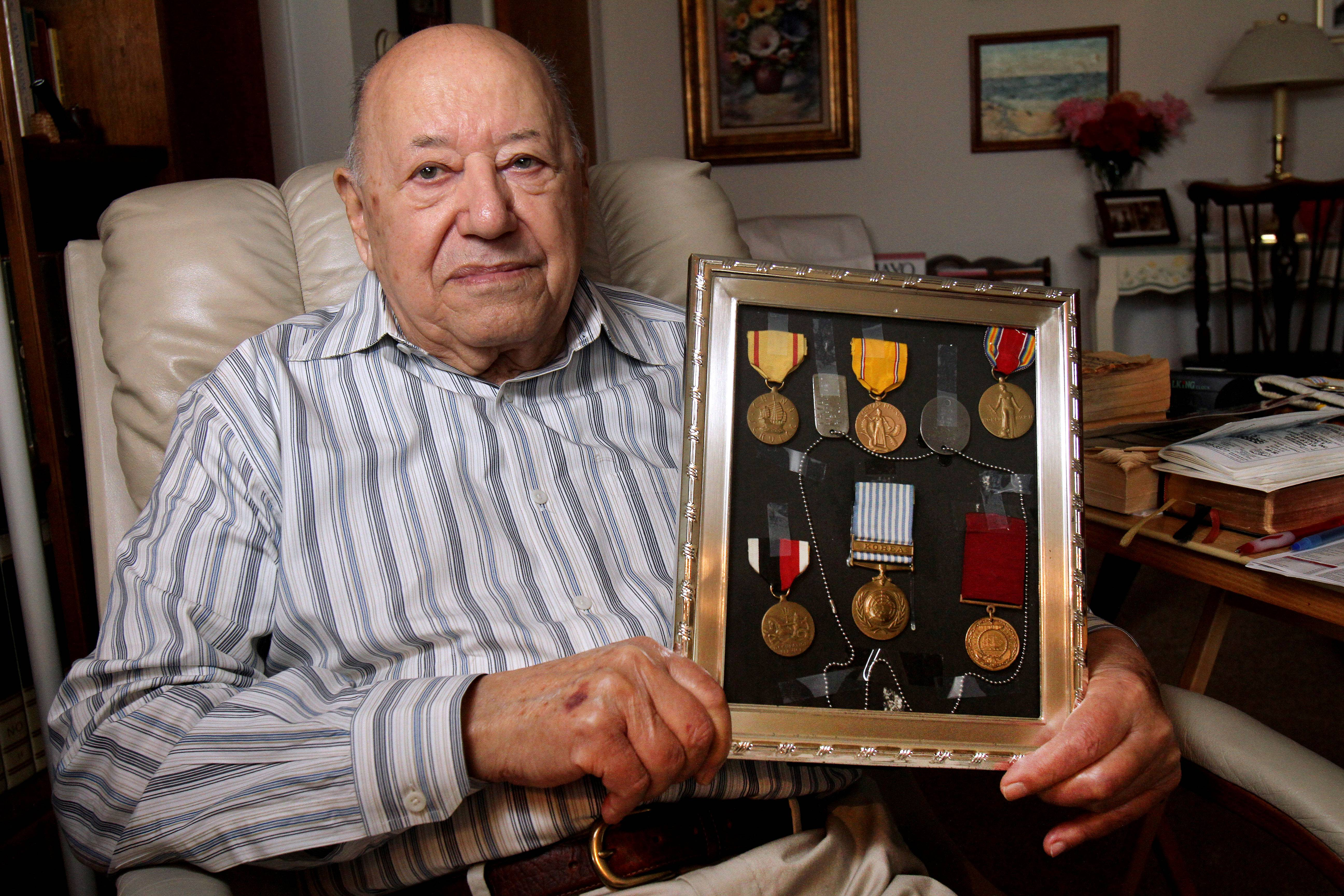 Pearl Harbor attack survivor Joe Triolo holds medals he earned while serving in World War II and Korea.