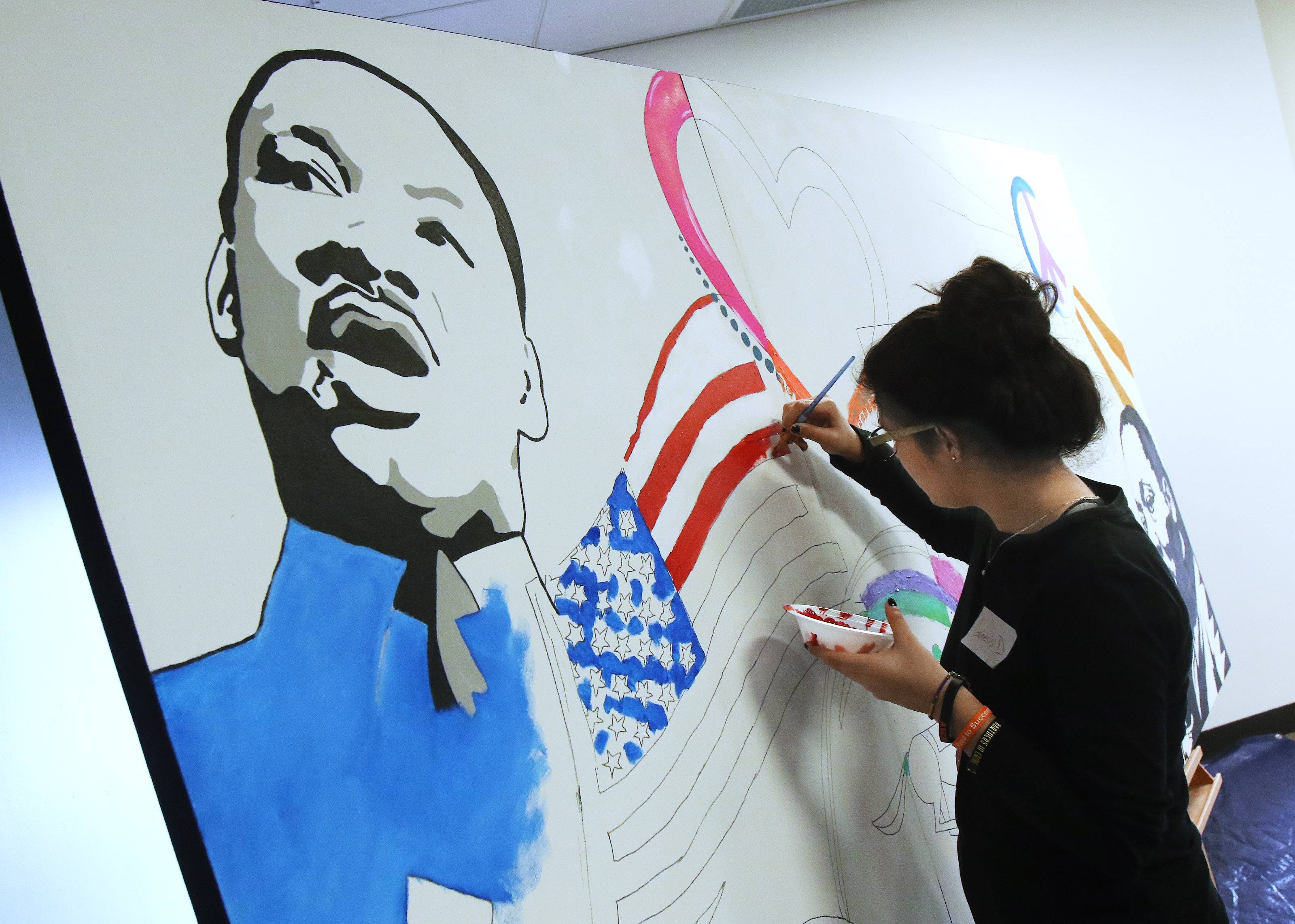 Genesis Davila, 15, of Elk Grove Village helps paint a mural honoring the life and legacy of Martin Luther King Jr. on Monday at the Arlington Heights Memorial Library.