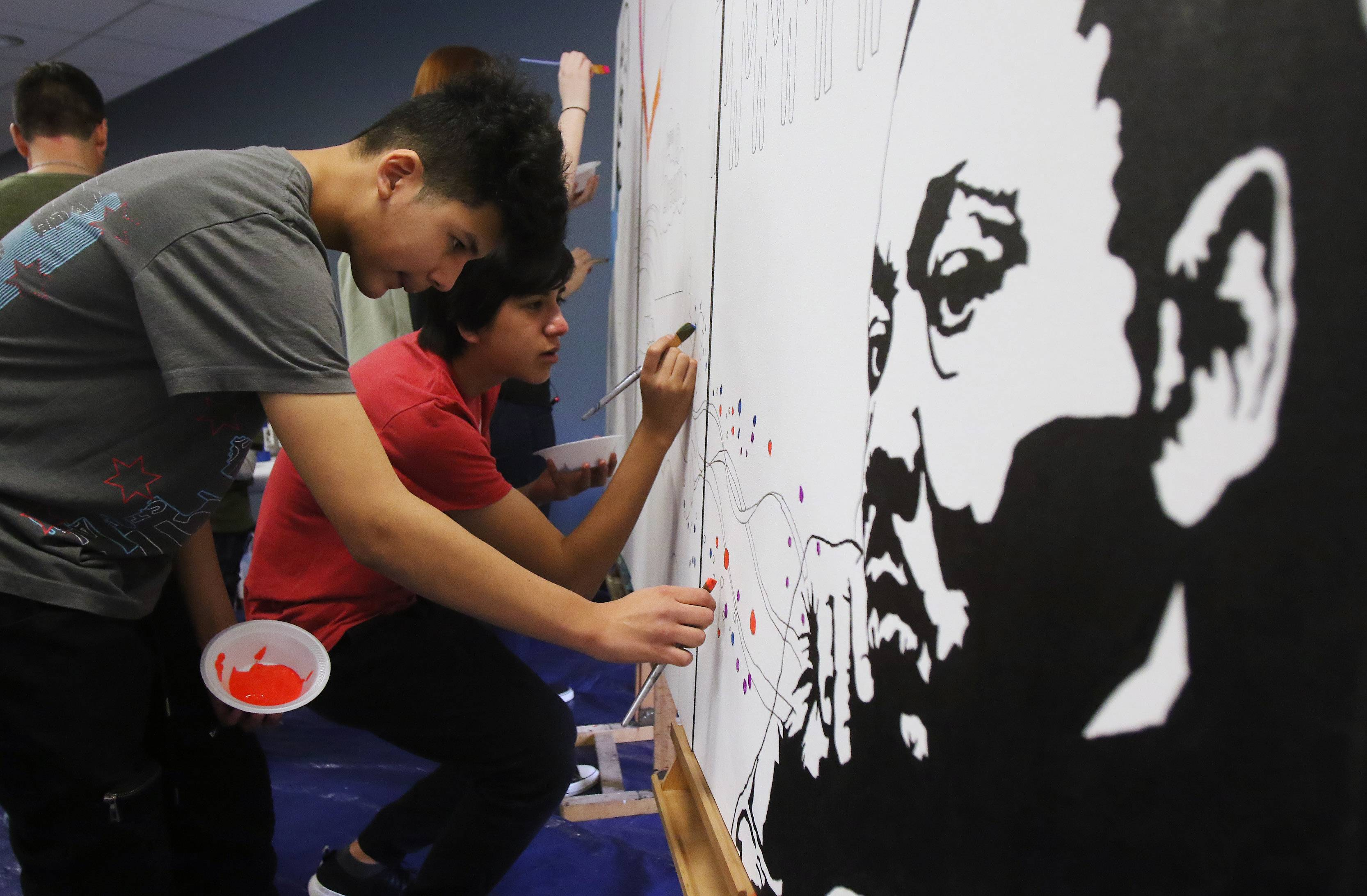 Marcos Vasquez, 14, of Rolling Meadows, left, and Francisco Cedillo, 16, of Mount Prospect help paint a mural honoring the life and legacy of Martin Luther King Jr. on Monday at the Arlington Heights Memorial Library.