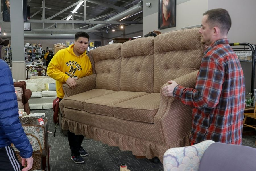 Henry Hartl, left, a junior and member of the wrestling team at Metea Valley High School in Aurora, helps move a couch Monday with Jesse Reeder, a resident of Wayside Cross Ministries in Aurora. The students were helping out as part of the school's Dr. Martin Luther King Jr. Day of Service.
