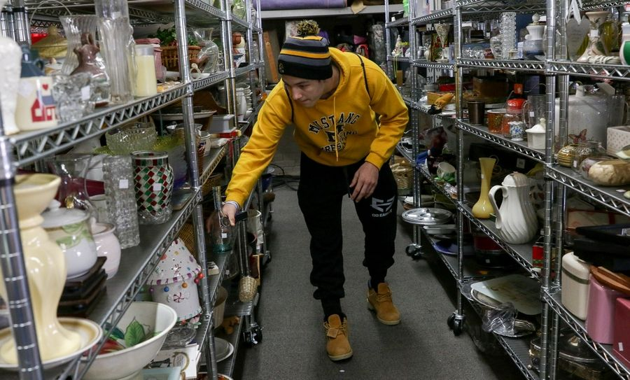 Josh La Barbera, a sophomore and wrestler at Metea Valley High School in Aurora, helps sort items Monday at the Hope Chest resale store, which benefits Wayside Cross Ministries in Aurora.