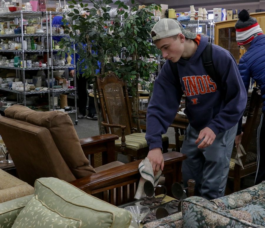 Kyle Smart, a junior and wrestler at Metea Valley High School in Aurora, helps clean furniture Monday at the Hope Chest resale store.