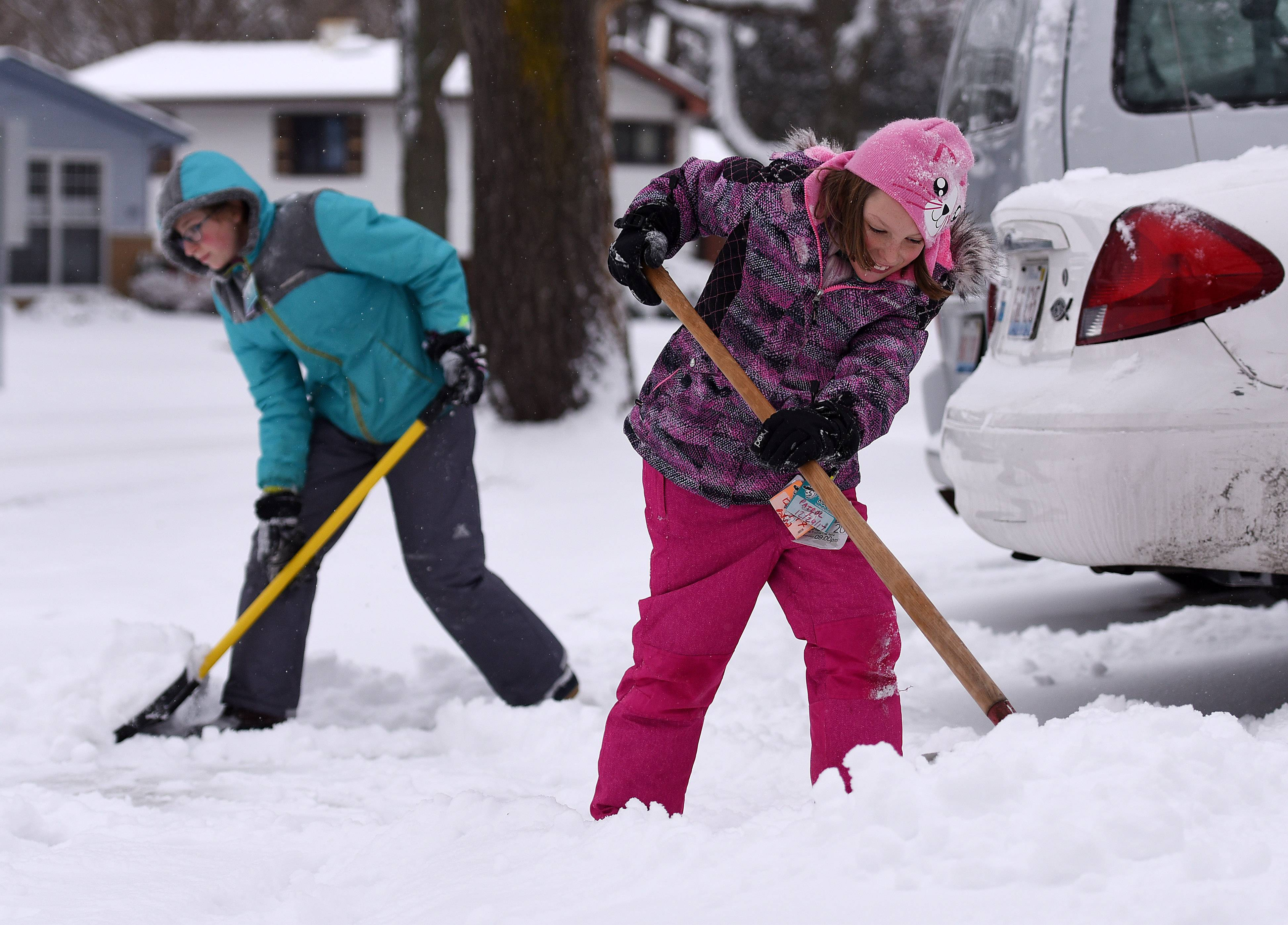 Sisters Lindsay, 10, right, and Kali Strossner, 13, help shovel the driveway of a neighbor in West Dundee Monday after several inches of snow fell overnight around the Fox Valley.