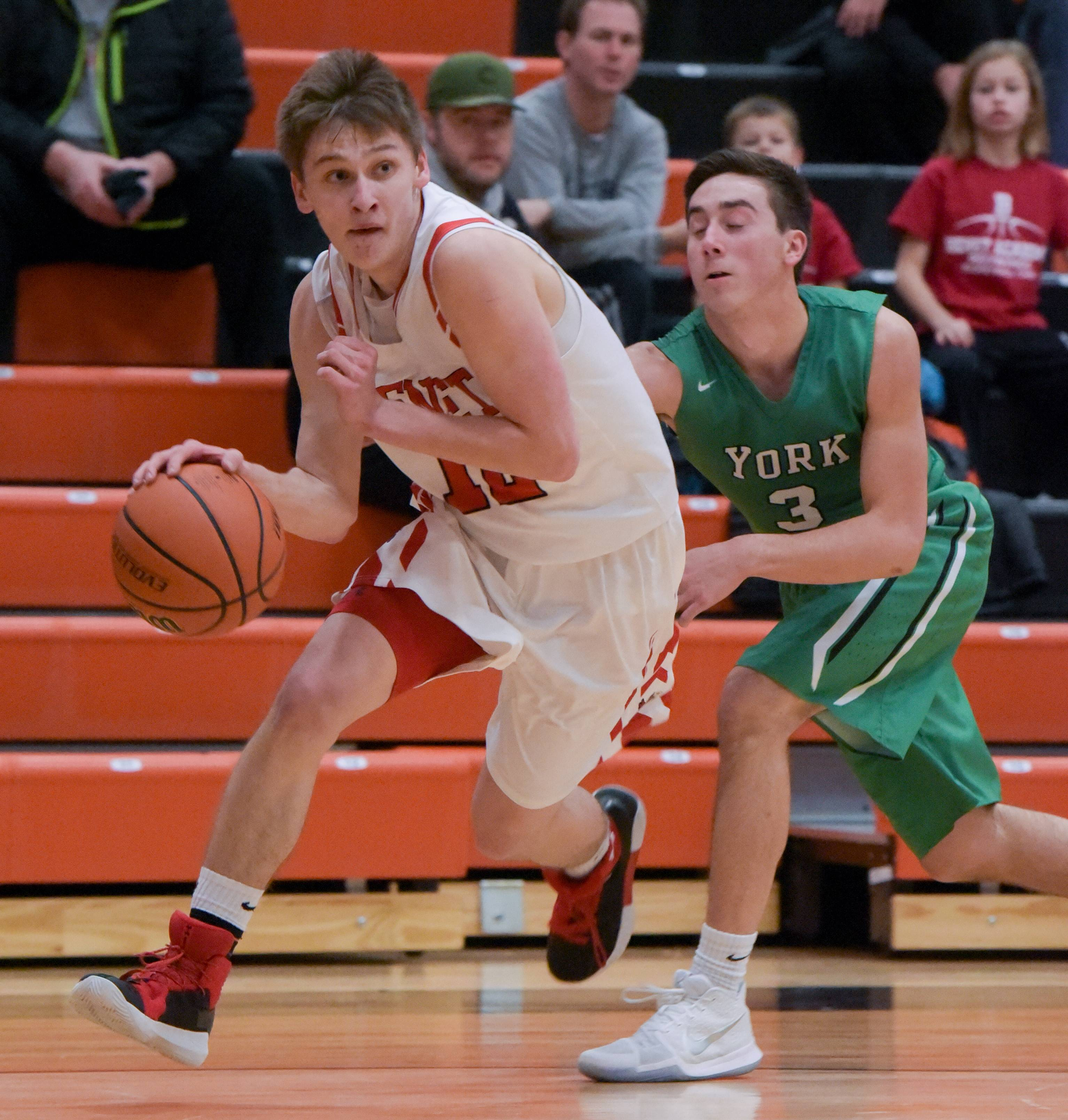Benet's David Buh (12) moves past York's Nicholas Kosich (3) during the semifinals of the 6th annual MLK Wheaton Warrenville South boys basketball tournament on Monday, Jan. 15, 2018.