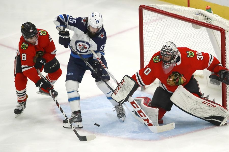 b192c772c73 Chicago Blackhawks center Nick Schmaltz (8) and goaltender Jeff Glass (30)  defend