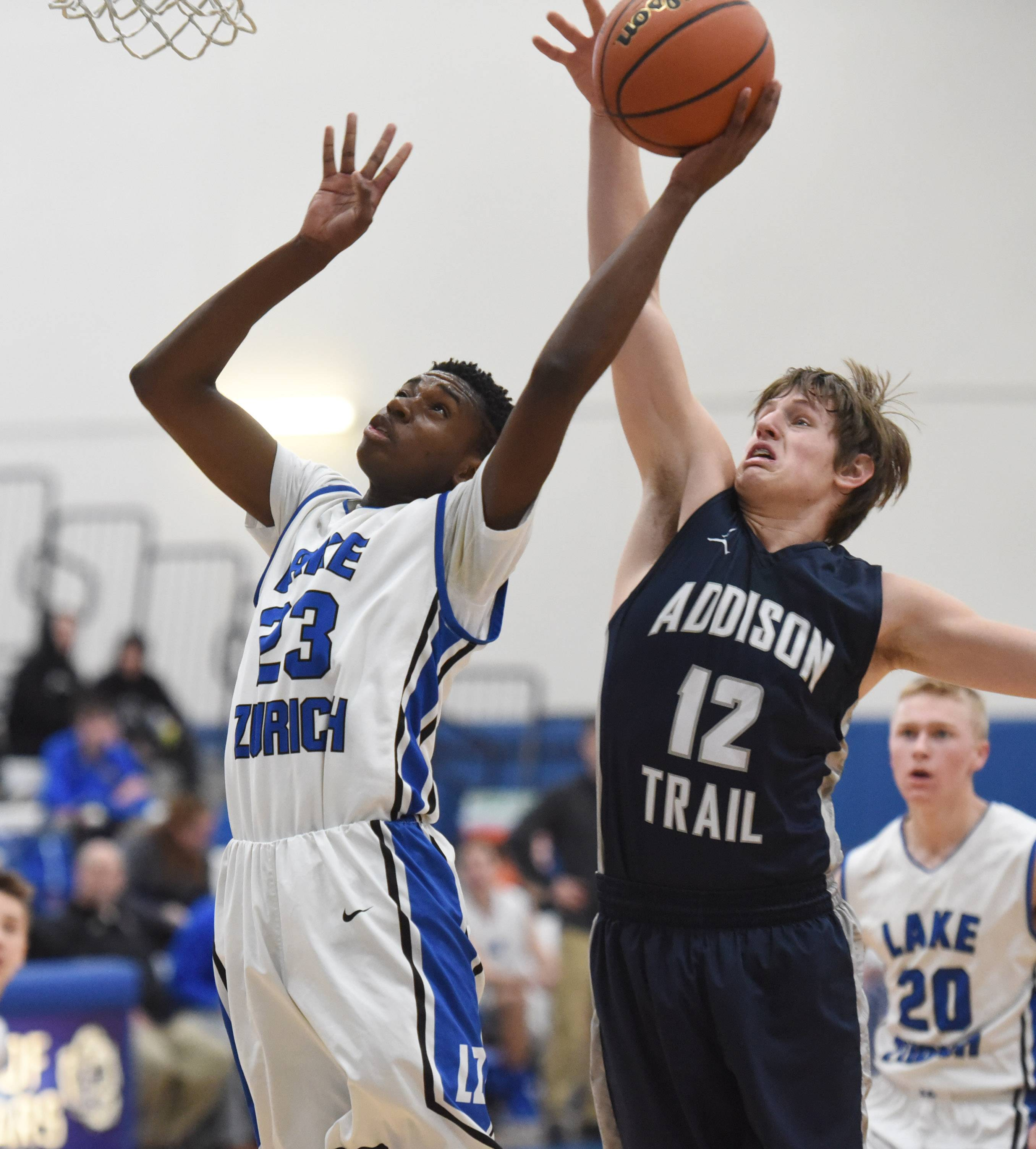 Lake Zurich's Kenny Haynes (23) goes to the hoop under defensive pressure of Addison Trail's A.J. Parnell during Monday's basketball game in Lake Zurich.