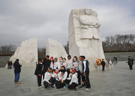 Members of the University of the District of Columbia women's lacrosse team stop to take a group photo at the Martin Luther King Jr., Memorial on the National Mall in Washington, Monday, Jan. 15, 2018.