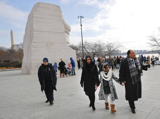 Martin Luther King III, right, holds hands with his wife Arndrea Waters, center, and their daughter Yolanda, 9, during their visit to the Martin Luther King Jr., Memorial on the National Mall in Washington, Monday, Jan. 15, 2018. The son of the late U.S. civil rights activist Martin Luther King Jr., and his family had earlier participated in an event commemorating the life and legacy of his father.