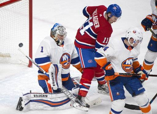 New York Islanders goaltender Thomas Greiss (1) is scored on by Montreal Canadiens left wing Max Pacioretty, not shown, as right wing Brendan Gallagher (11) and Islanders defenseman Thomas Hickey (14) look for the rebound during the third period of an NHL hockey game in Montreal, Monday, Jan. 15, 2018. (Graham Hughes/The Canadian Press via AP)