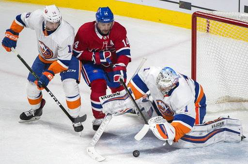 New York Islanders goaltender Thomas Greiss (1) makes a save against Montreal Canadiens center Tomas Plekanec (14) as Islanders center Alan Quine (10) defends during second-period NHL hockey game action in Montreal, Monday, Jan. 15, 2018. (Graham Hughes/The Canadian Press via AP)