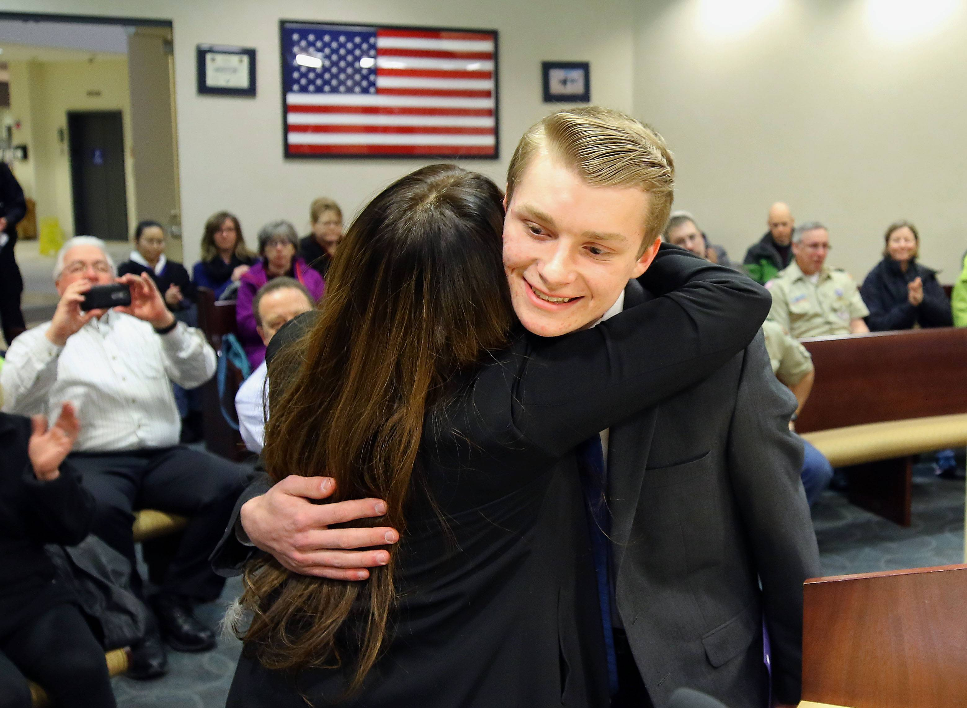 Fremd High School student Tyler Matuszczak of Hoffman Estates, right, gets a hug from Sneha Dixit, whose father Matuszczak saved by performing CPR after the man collapsed from a heart attack on his driveway. Matuszczak received a Citizen Lifesaving Award at Monday's Hoffman Estates village board meeting.