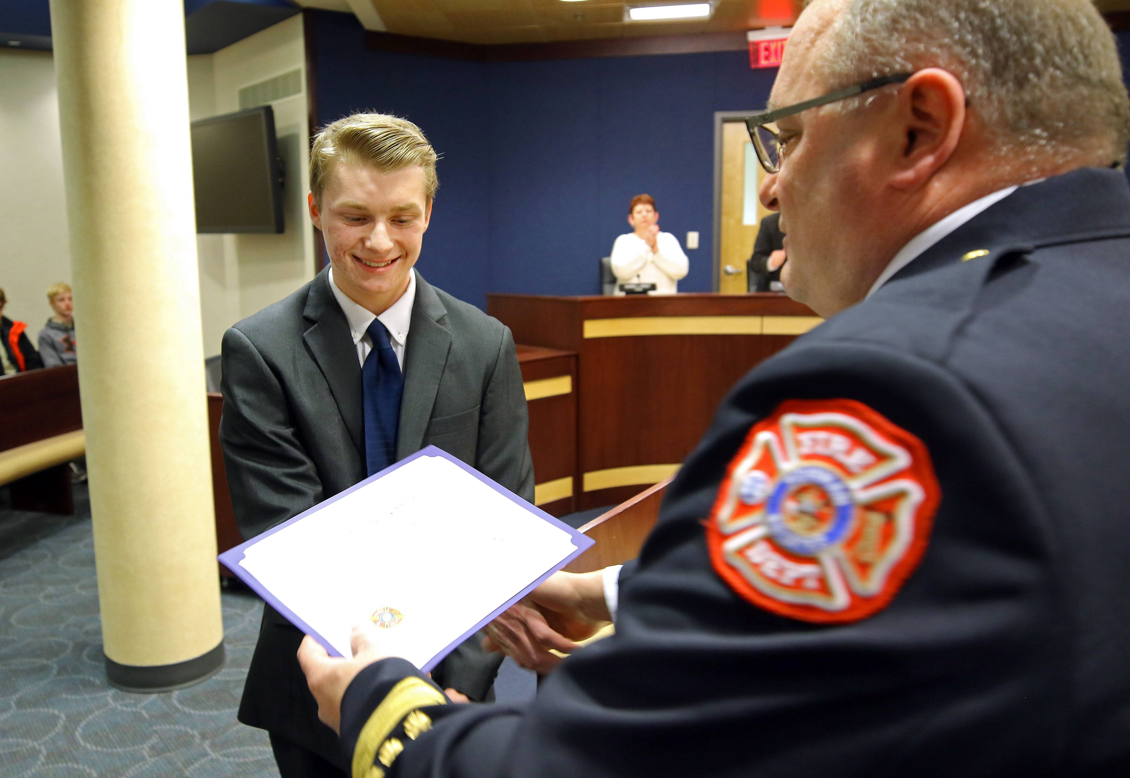 Fremd High School student Tyler Matuszczak of Hoffman Estates, left, receives a Citizen Lifesaving Award from Hoffman Estates Fire Chief Patrick Fortunato at Monday's Hoffman Estates village board meeting. Matuszczak performed CPR on a neighbor who'd collapsed from a heart attack on his driveway.