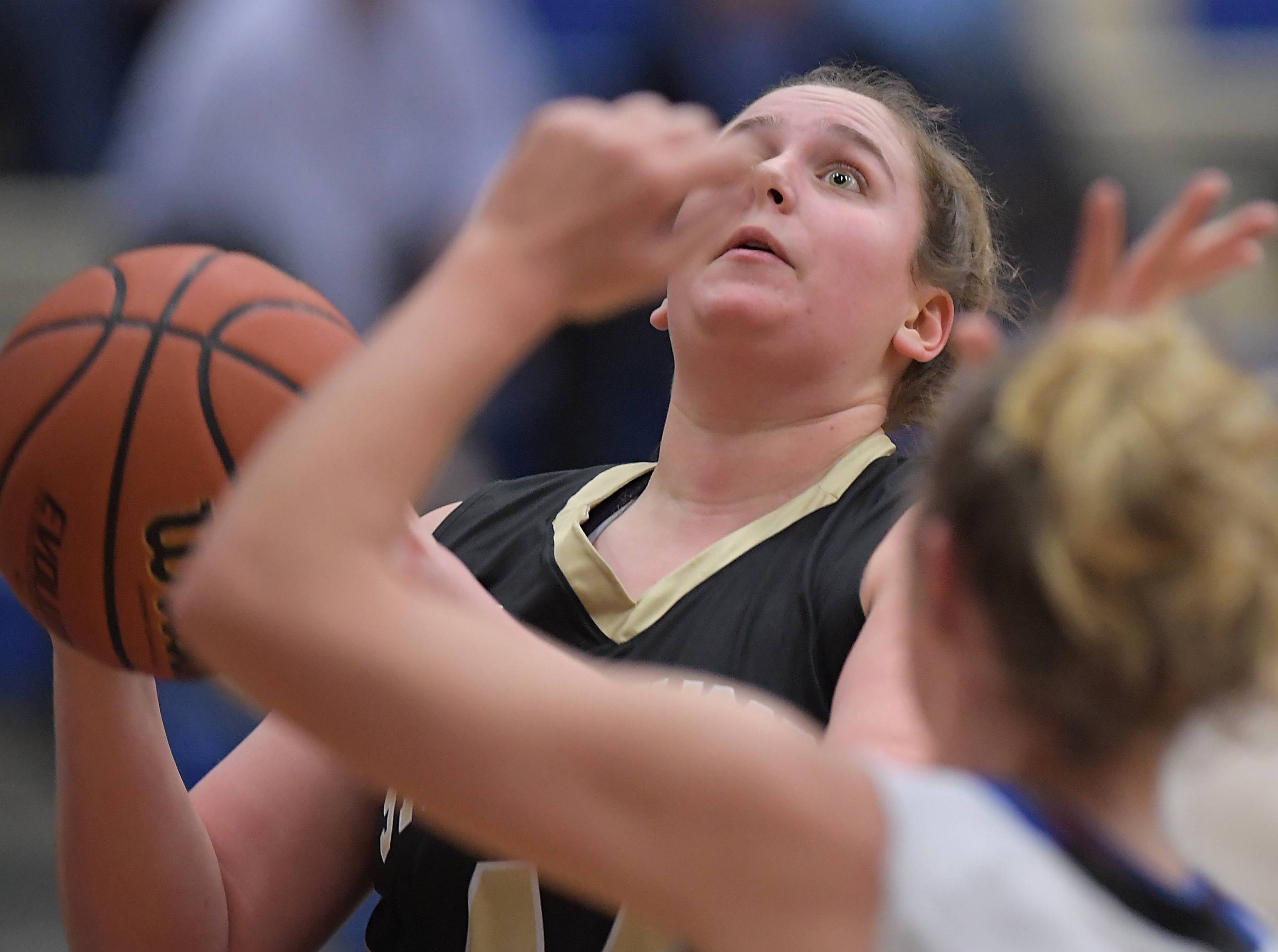 Streamwood's Becky Roncone eyes the basket as she goes against Geneva's Emma Kornak during a girls basketball game Tuesday in Geneva.