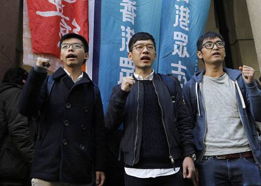 Pro-democracy activists, from left, Joshua Wong, Nathan Law and Alex Chow, shout slogans in front of the Court of Final Appeal Hong Kong, Tuesday, Jan. 16, 2018. Three young Hong Kong activists are making a last-ditch attempt to overturn prison sentences for their roles in sparking 2014's massive pro-democracy protests in the semiautonomous Chinese city. (AP Photo/Vincent Yu)