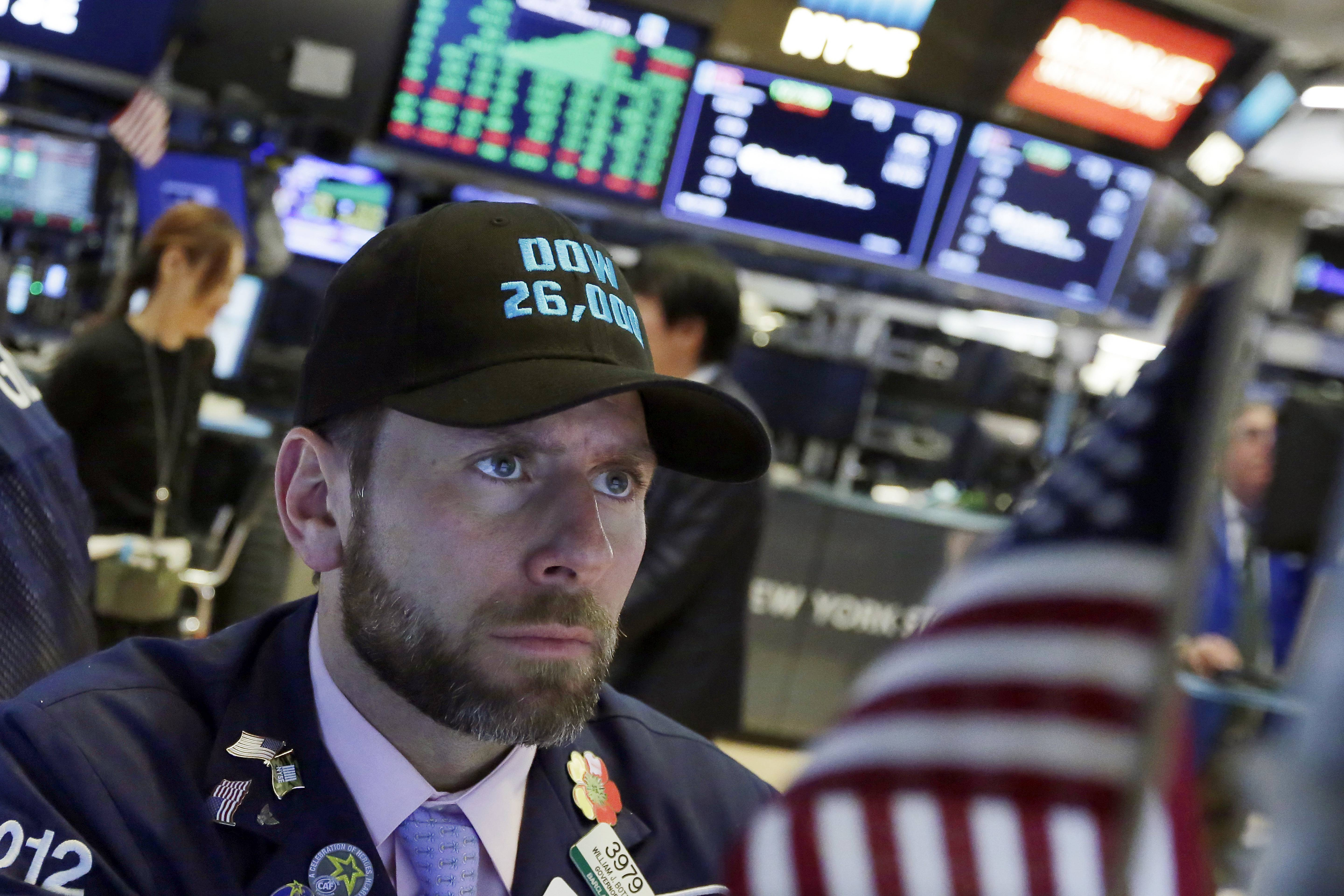 "Specialist Michael Pistillo wears a ""Dow 26,000"" hat as he works on the floor of the New York Stock Exchange, Wednesday, Jan. 17, 2018. Stocks are closing higher on Wall Street, sending the DJIA to its first close above 26,000 points. (AP Photo/Richard Drew)"