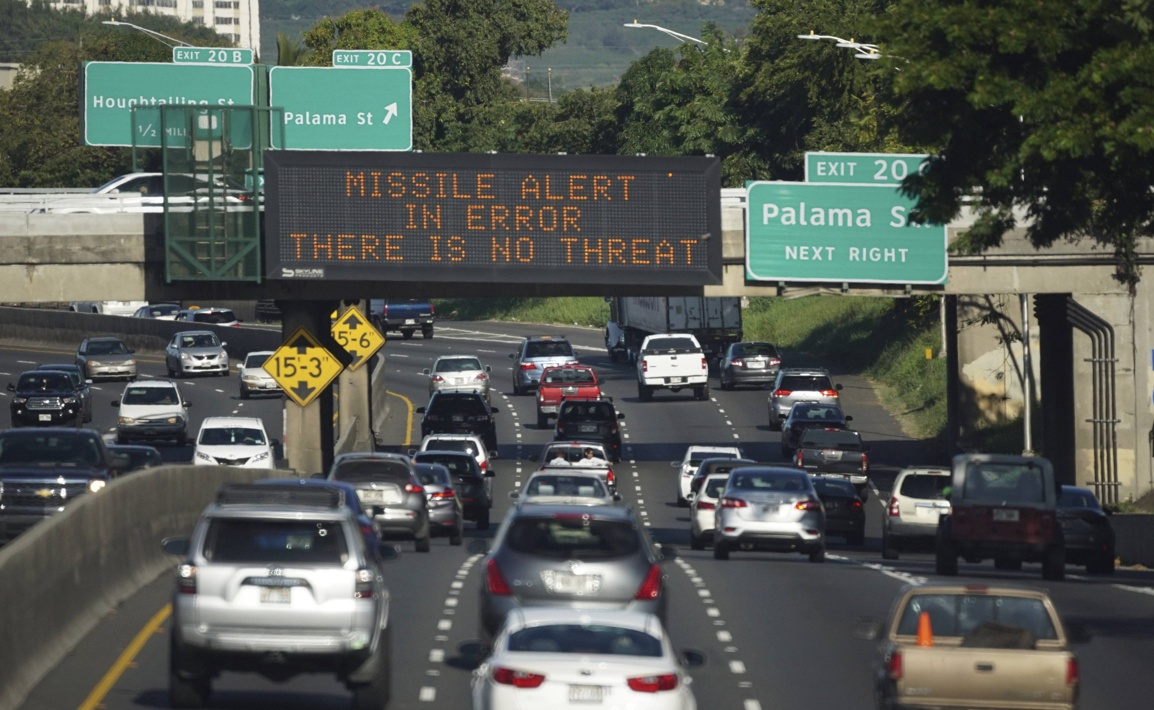 Cars drive past a highway sign canceling a missile threat in Hawaii. State emergency officials said human error caused a statewide announcement of an incoming missile strike alert that was sent to mobile phones.