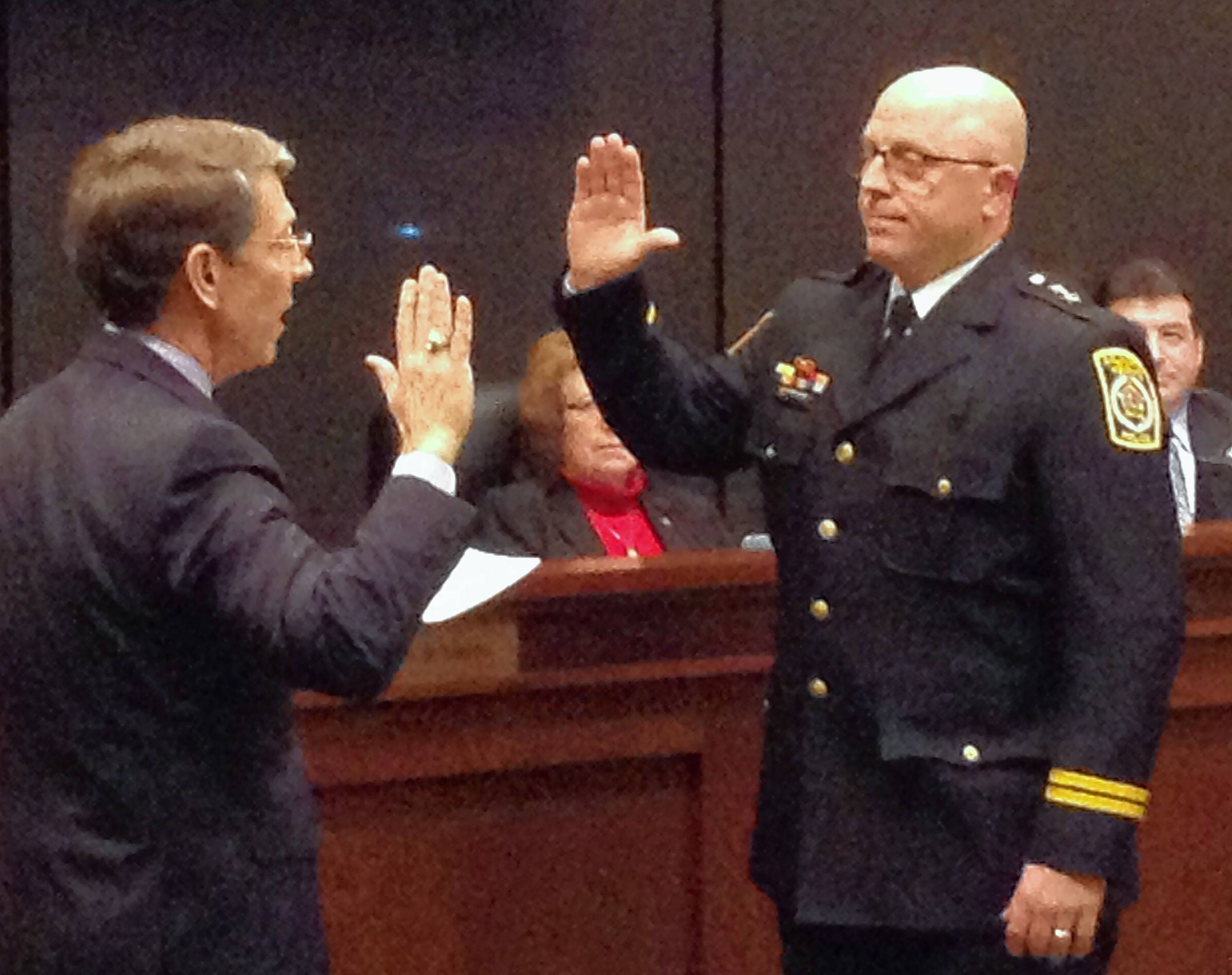 Nathan Hayes, right, is sworn in as deputy police chief Tuesday by Arlington Heights Mayor Tom Hayes.