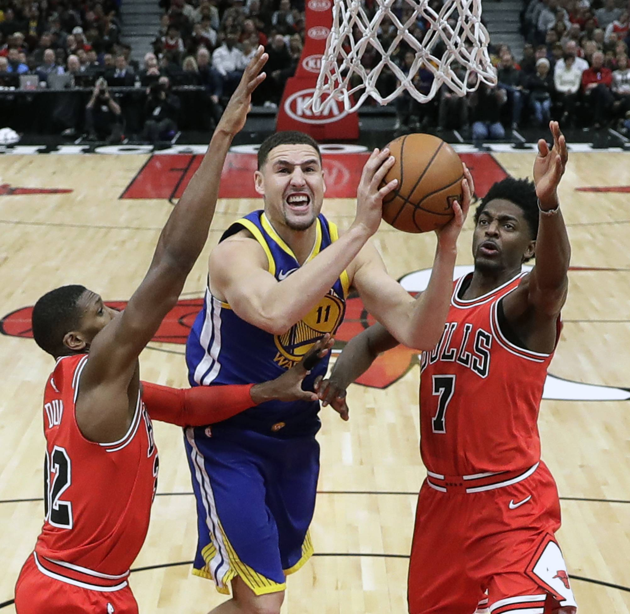 Golden State Warriors' Klay Thompson (11) shoots between Chicago Bulls' Kris Dunn (32) and Justin Holiday, right, during the second half of an NBA basketball game Wednesday, Jan. 17, 2018, in Chicago. The Warriors won 119-112.