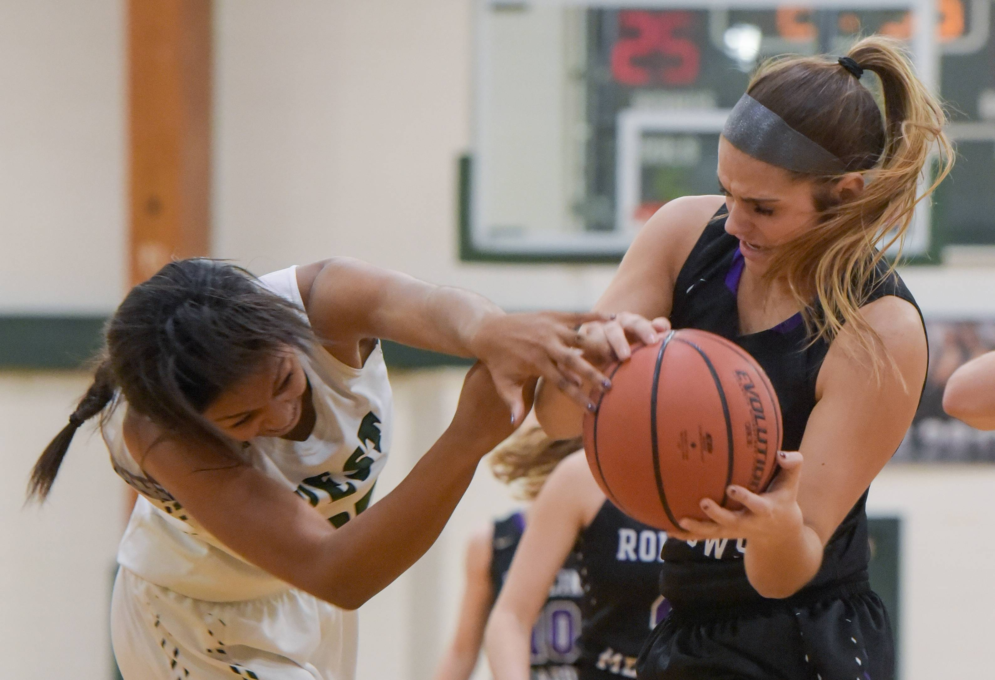 Glenbard West's Jamiyah Thomas (25) and Rolling Meadows' Elise Kowalski (23) struggle for control of the ball.