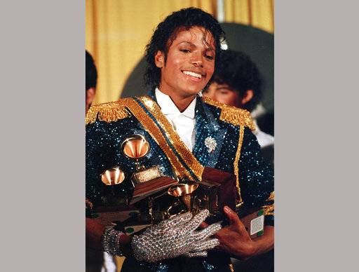 FILE - In this Feb. 28, 1984 file photo, Michael Jackson appears backstage with his signature rhinestone glove at the 26th annual Grammy Awards in Los Angeles as he poses with the awards he won in eight different categories. (AP Photo/Reed Saxon, File)