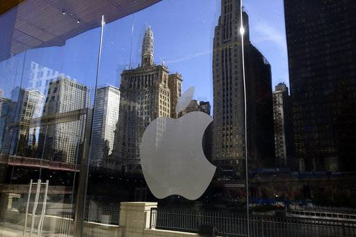 FILE - In this Thursday, Oct. 19, 2017, file photo, buildings and a tour boat are reflected on the mirror behind an Apple logo during a preview event at a new Apple Michigan Avenue store, in downtown Chicago. On Wednesday, Jan. 17, 2018, Apple announced it is planning to build another corporate campus and hire 20,000 workers during the next five years as part of a $350 billion commitment to the U.S. economy. (AP Photo/Kiichiro Sato, File)