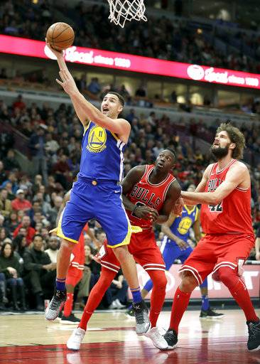 Golden State Warriors' Klay Thompson (11) scores past Chicago Bulls' Robin Lopez (42) and Jerian Grant during the first half of an NBA basketball game Wednesday, Jan. 17, 2018, in Chicago. (AP Photo/Charles Rex Arbogast)
