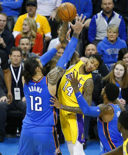 Los Angeles Lakers forward Brandon Ingram (14) passes between Oklahoma City Thunder center Steven Adams (12) and forward Paul George, right, in the first half of an NBA basketball game in Oklahoma City, Wednesday, Jan. 17, 2018. (AP Photo/Sue Ogrocki)