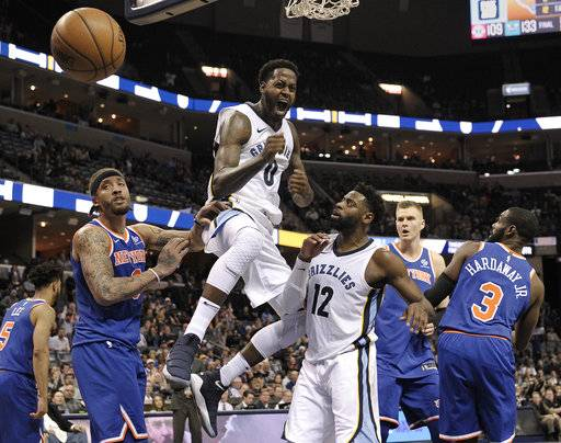 Memphis Grizzlies forward JaMychal Green (0) reacts after dunking the ball as New York Knicks forward Michael Beasley, from left, Grizzlies guard Tyreke Evans (12), and Knicks forwards Kristaps Porzingis and Tim Hardaway Jr. (3) look on in the second half of an NBA basketball game Wednesday, Jan. 17, 2018, in Memphis, Tenn. (AP Photo/Brandon Dill)