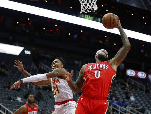 New Orleans Pelicans center DeMarcus Cousins (0) collects a rebound in front of Atlanta Hawks guard Kent Bazemore (24) during the first half of an NBA basketball game Wednesday, Jan. 17, 2018, in Atlanta. (AP Photo/John Bazemore)