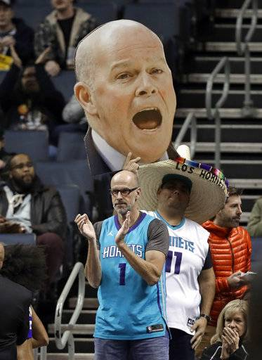 A Charlotte Hornets fan holds with a large photo of Charlotte Hornets head coach Steve Clifford during the first half of an NBA basketball game against the Washington Wizards in Charlotte, N.C., Wednesday, Jan. 17, 2018. Clifford returned to the bench after being out for several weeks for a health issue. (AP Photo/Chuck Burton)
