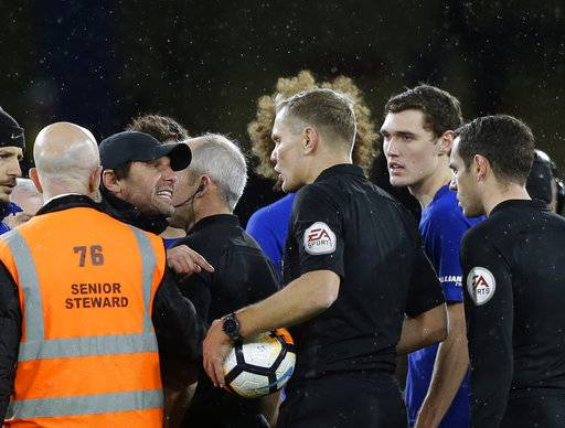 Referee Graham Scott, center, discusses with Chelsea's manager Antonio Conte during the English FA Cup third round replay between Chelsea and Norwich City at the Stamford Bridge, in London, Wednesday, Jan. 17, 2018. (AP Photo/Alastair Grant)