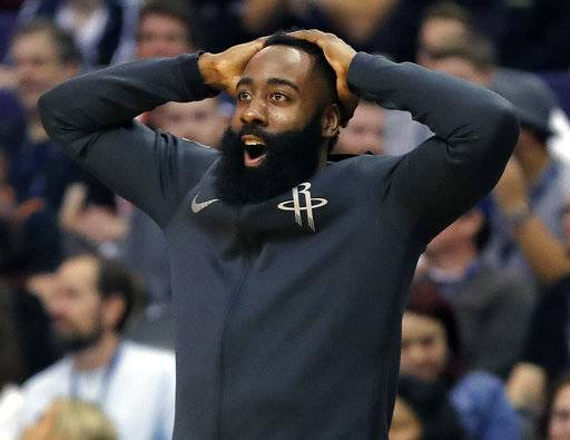 Houston Rockets guard James Harden reacts from the bench to a teammate's dunk against the Phoenix Suns during the second half of an NBA basketball game Friday, Jan. 12, 2018, in Phoenix. (AP Photo/Matt York)