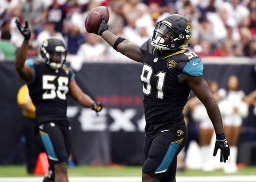 FILE- In this Sept. 10, 2017, file photo, Jacksonville Jaguars defensive end Yannick Ngakoue (91) celebrates after he recovered a fumble by Houston Texans quarterback Deshaun Watson during the second half of an NFL football game in Houston. The second-year pro led the NFL with six forced fumbles in the regular season and added another one last week at Pittsburgh. Ngakoue would love to add New England's Tom Brady to his growing resume in the AFC championship game. (AP Photo/Eric Christian Smith, File)