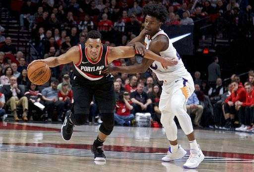 Portland Trail Blazers guard Evan Turner, left, dribbles past Phoenix Suns forward Josh Jackson during the first half of an NBA basketball game in Portland, Ore., Tuesday, Jan. 16, 2018.