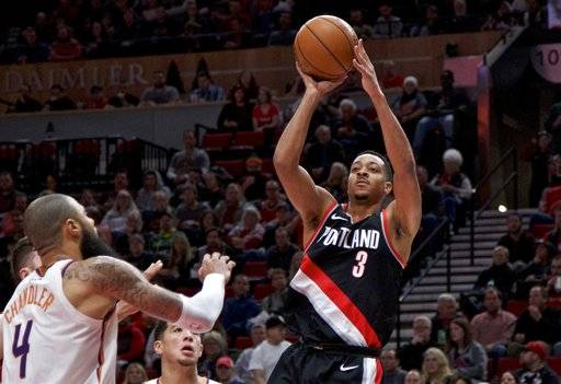 Portland Trail Blazers guard CJ McCollum, right, shoots over Phoenix Suns center Tyson Chandler during the first half of an NBA basketball game in Portland, Ore., Tuesday, Jan. 16, 2018.