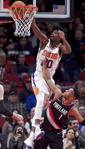 Phoenix Suns forward Josh Jackson, left, dunks over Portland Trail Blazers guard Evan Turner during the first half of an NBA basketball game in Portland, Ore., Tuesday, Jan. 16, 2018.