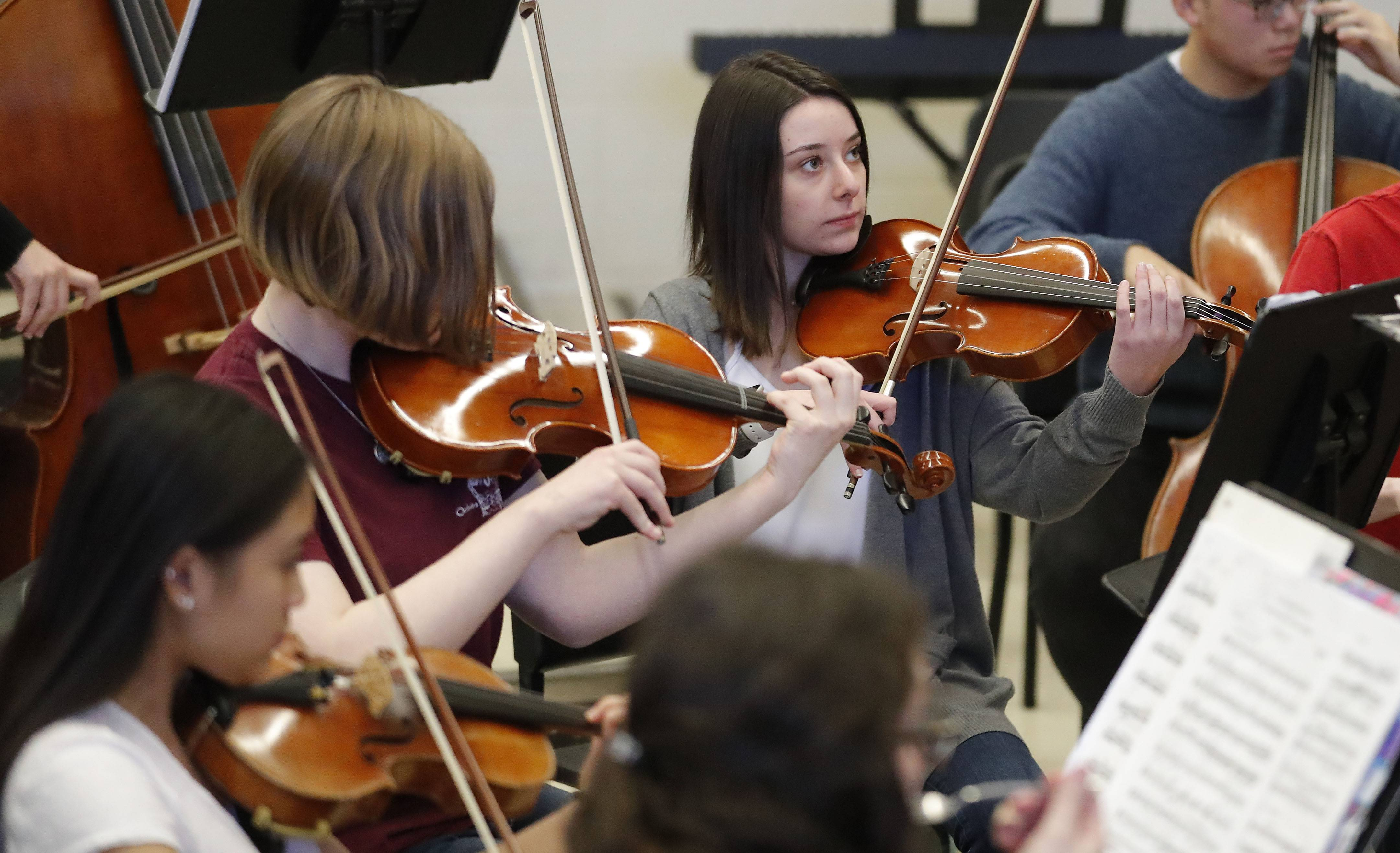 "Katie Gordon, far right, plays her viola during a Buffalo Grove High School chamber orchestra rehearsal of an original composition, ""Solaces,"" in tribute to three teachers who died last school year."