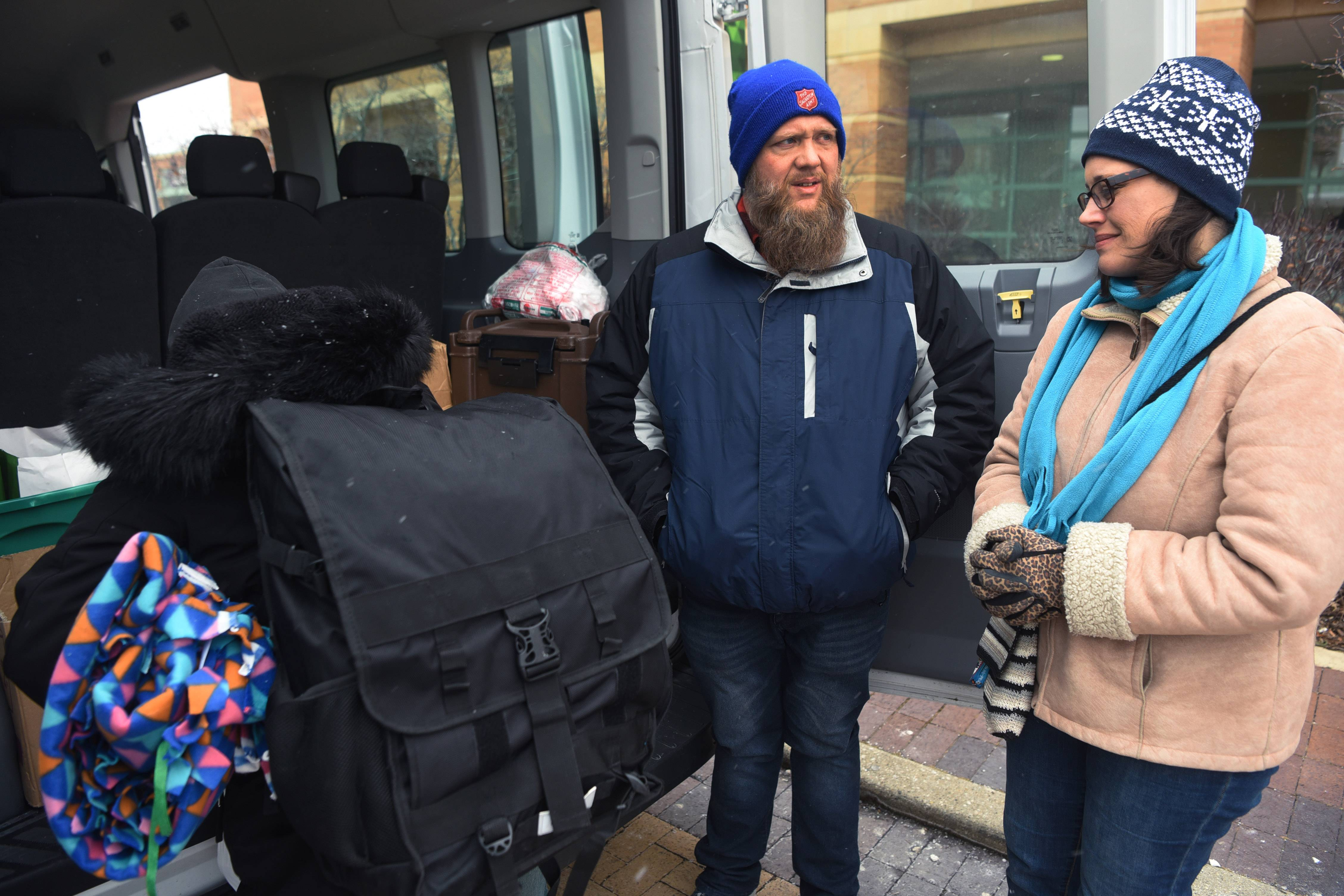 After fetching her a blanket from the back of their Salvation Army van in Des Plaines, Bill and Debbi Middendorp help a homeless woman choose from a selection of food items.