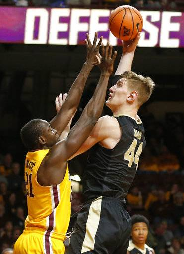 Purdue's Isaac Haas, right, shoots over Minnesota's Bakary Konate of Mali in the first half of an NCAA college basketball game Saturday, Jan. 13, 2018, in Minneapolis.