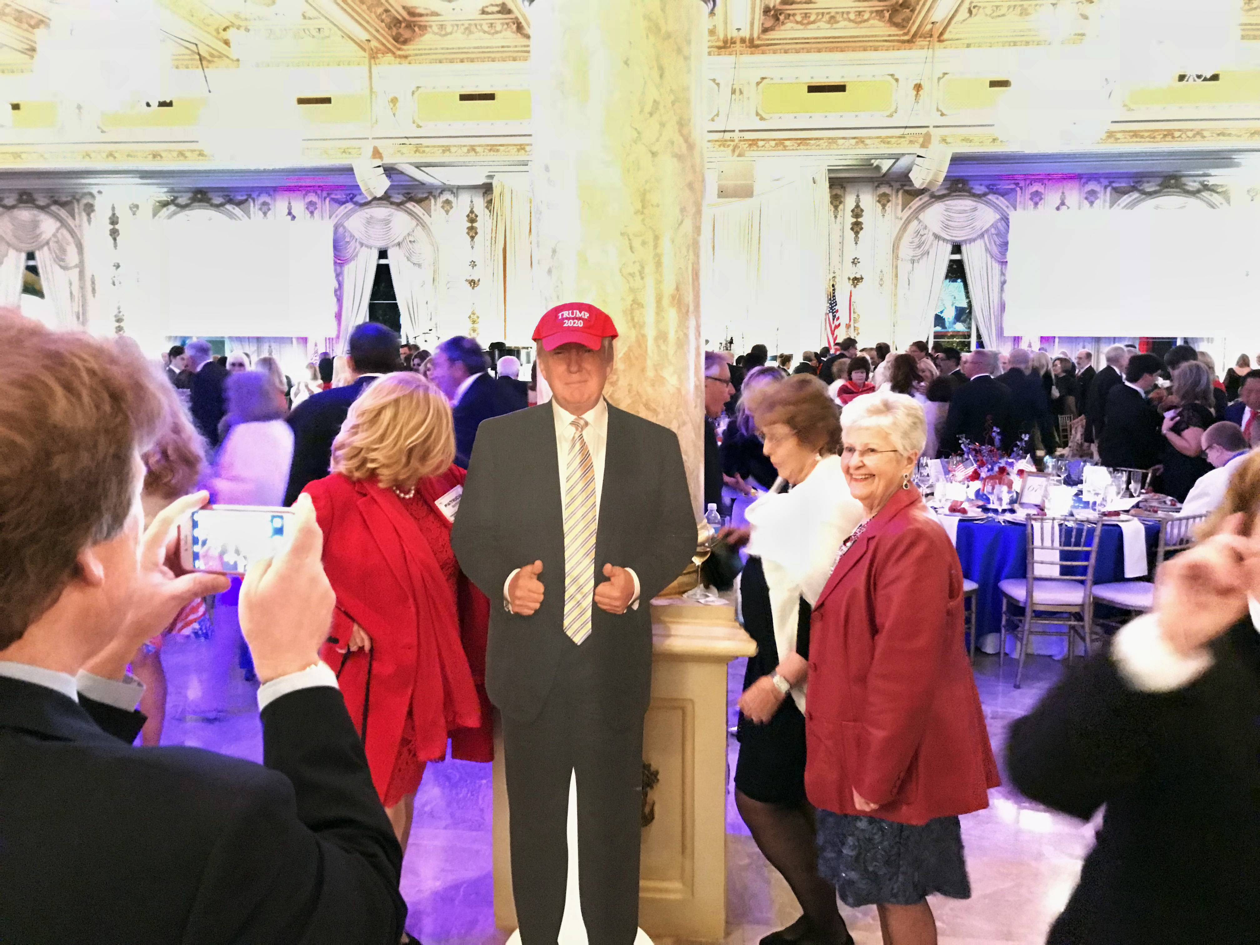 Supporters of President Donald Trump pose with a cardboard cutout at the entrance to the Donald J. Trump Grand Ballroom at Trump's Mar-a-Lago Club in Palm Beach, Florida.