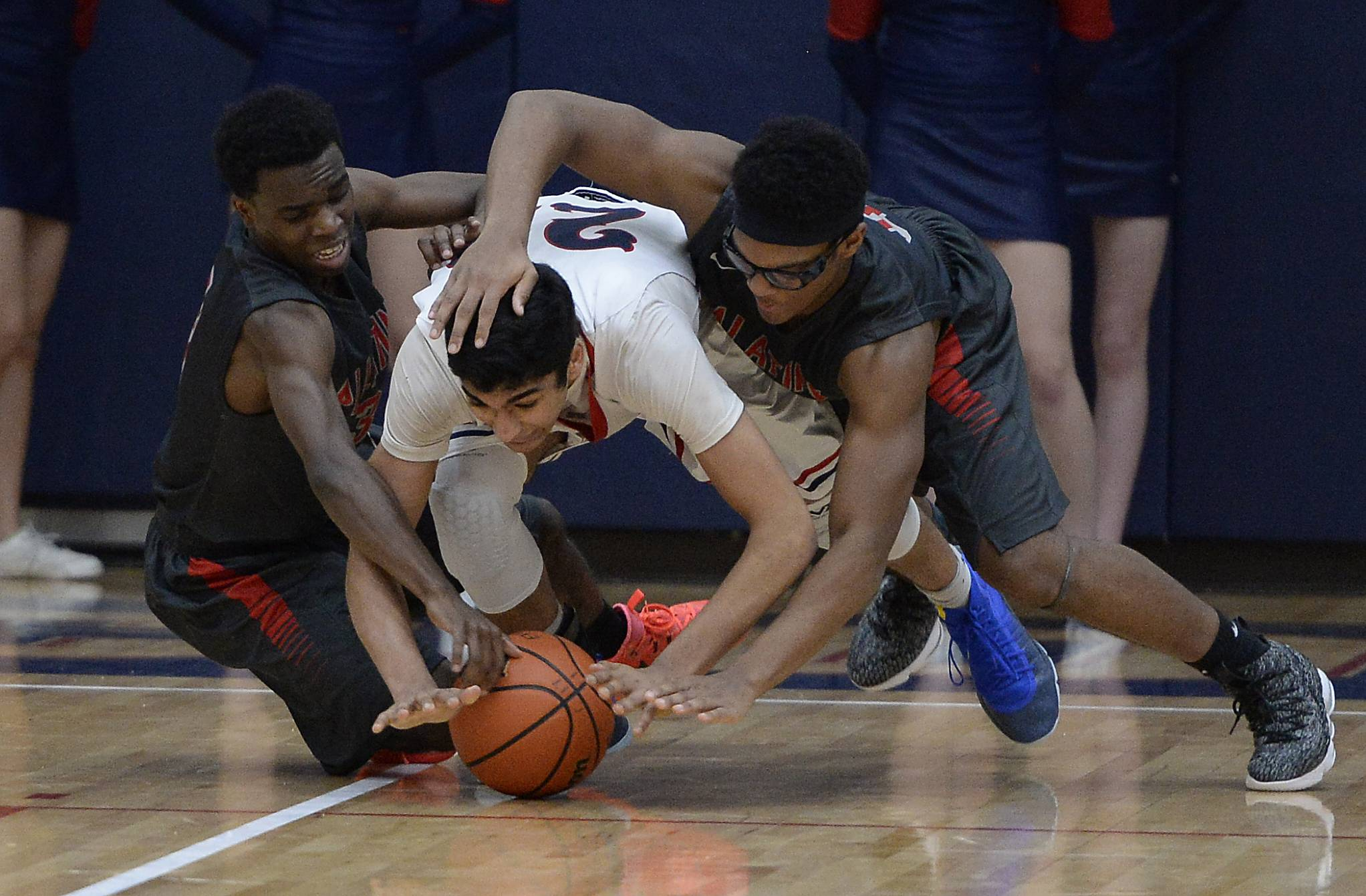 Palatine's Demareon Collins and teammate Cortez Hogans follow Conant's Rajat Mittal to the floor on a loose ball.