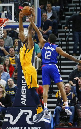 Utah Jazz forward Derrick Favors (15) goes to the basket as Los Angeles Clippers guard Tyrone Wallace (12) defends in the first half during an NBA basketball game Saturday, Jan. 20, 2018, in Salt Lake City.